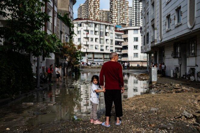 Un homme et une enfant se tiennent dans une rue inondée du quartier d'Esenyurt à Istanbul (Turquie) suite à de fortes pluies et à des tempêtes de grêle. 23 juin 2020. © Yasin AKGUL / AFP