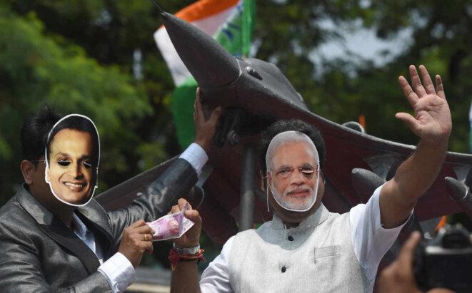 Des manifestants portent des masques du premier ministre indien Modi (droite) et d'Anil Ambani, devant la réplique d'un Rafale, à Bombay, en 2018. © Indranil Mukerjee / AFP
