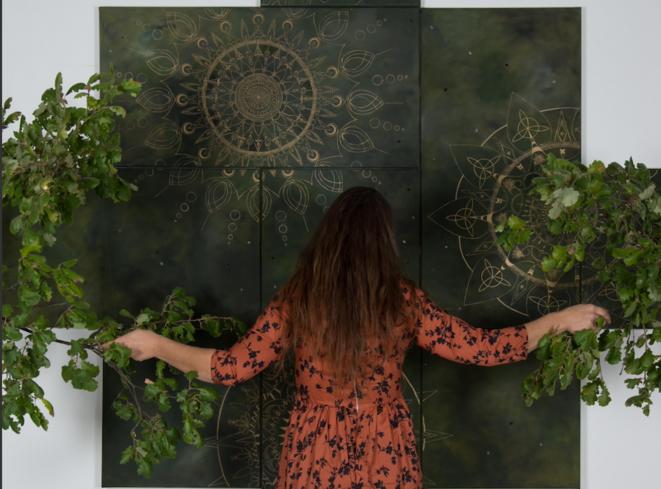 Isabelle Peru fait le contact à l'arbre avec l'une de ses œuvres dotée de branches