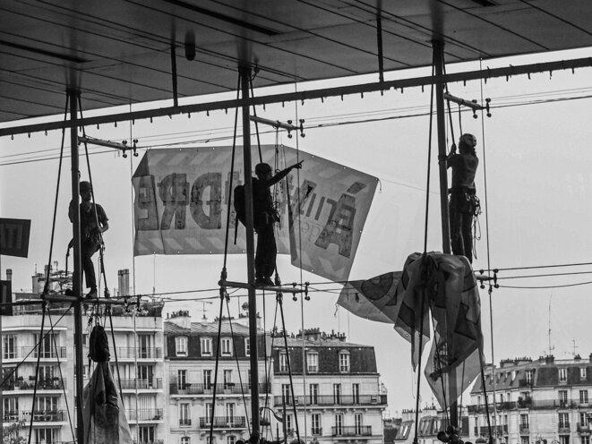 La vie ne tient qu'à un fil. Des militants suspendent une banderole lors de l'occupation d'un centre commercial à Paris, une action collective menée par Extinction Rebellion, le Comité Adama et les Gilets Jaunes, le 5 Octobre 2019. © P. Fimbel