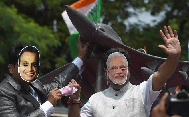 Mocking demonstrators in the Indian city of Mumbai in 2018 wearing masks of Indian Prime Minister Narendra Modi (right) and Reliance Group chairman and owner Anil Ambani standing in front of a replica model of a Rafale fighter jet. © Indranil Mukerjee / AFP