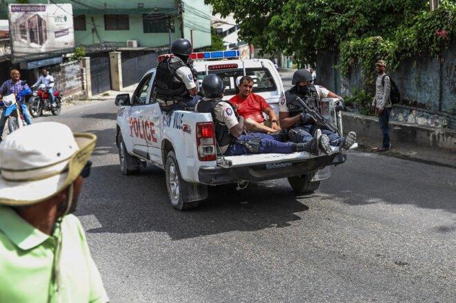 Deux hommes suspectés d'appartenir au commando ayant éliminé le président haïtien Jovenel Moïse sont transportés dans un véhicule de police à Port-au-Prince, le 8 juillet. © Valerie Baeriswyl / AFP