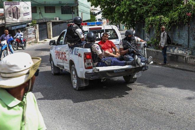 Dos hombres sospechosos de pertenecer al comando que eliminó al presidente haitiano Jovenel Moïse son transportados en un vehículo policial en Puerto Príncipe, el 8 de julio. © Valerie Baeriswyl/AFP