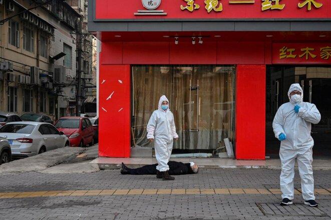 Wuhan, le 30 janvier 2020.  Des fonctionnaires en tenue de protection encadrent un homme décédé en pleine rue près d'un hôpital. © Photo Hector Retamal / AFP