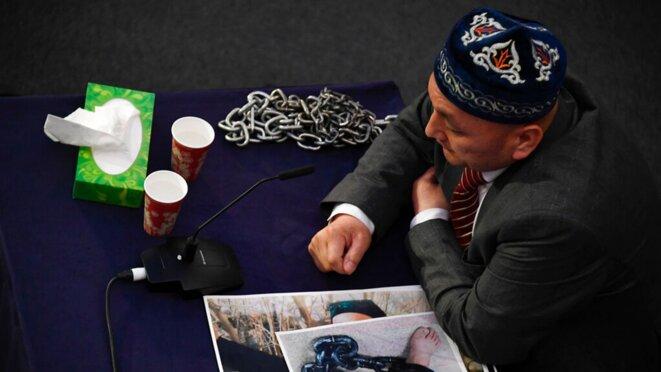 Un témoin témoigne devant le panel avec des images de pieds enchaînés. Photo: AP
