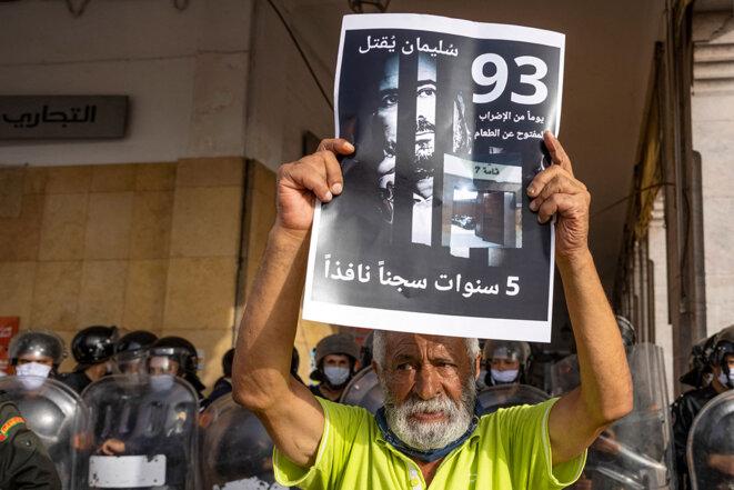 Un militant tient une banderole à l'effigie de Soulaimane Raissouni, lors de la manifestation de soutien aux journalistes emprisonnés, le 10 juillet 2021, à Rabat. © Photo Fadel Senna / AFP