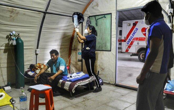 Santa Cruz, le 13 juillet 2020. Des médecins volontaires membres de l'organisation «Les anges contre Covid», assistent un patient malade du Covid-19 dans leur hôpital sous tente. Cette organisation vient répondre à la saturation du système de santé bolivien. © Photo Enrique CANEDO / AFP