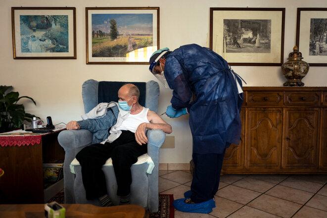 Vaccination d'un homme de plus de 80 ans contre le Covid-19, le 13 mars 2021 à Dronero, en Italie. © Photo de Marco Bertorello / AFP