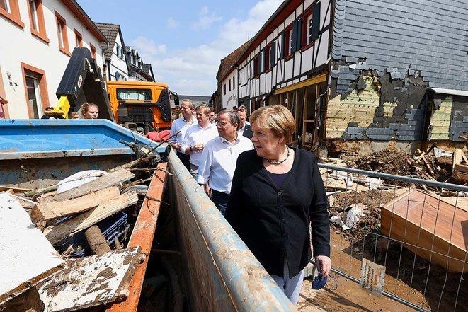 La canciller alemana, Angela Merkel, con el candidato conservador a las elecciones, Armin Laschet, justo detrás de ella, mientras viajan a IIversheim para comprobar los daños causados por las inundaciones. © Foto Wolfgang Rattay/Reuters/Pool/vía AFP