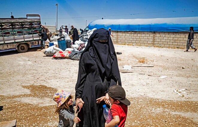 Une femme avec ses enfants, dans le camp d'Al-Hol, qui abrite des proches de combattants du groupe État islamique, dans le nord-est de la Syrie, en mai 2021. © Photo Delil Souleiman / AFP