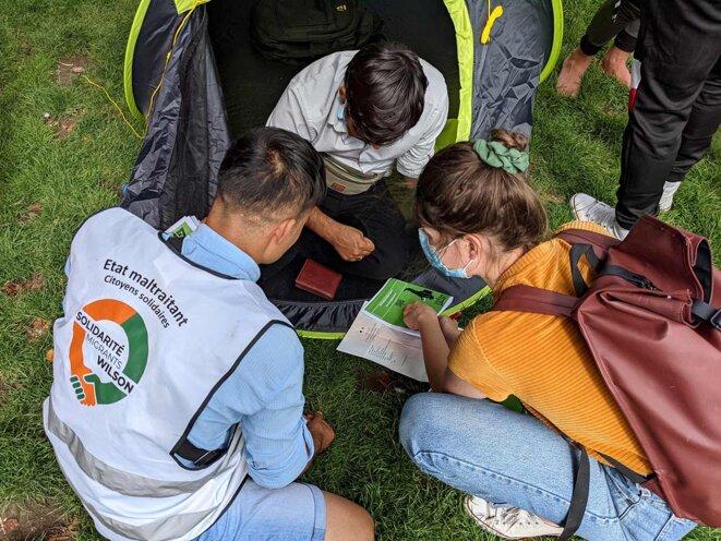 Pour aider ceux qui ont essuyé des refus de demandes d'asile ou de minorité, Pauline distribue des guides d'information juridique édités par l'association Watizat. © Photo Rémi Yang pour Mediapart