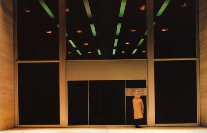 L'architecture gigantesque et froide de l'imposante façade de l'immeuble contre laquelle se cogne la solitude de Lotte, déréalise l'ensemble. Aux lignes droites acérées et dures du métal et du bois brut, répond, ironiquement, la fausse perspective en biais de lueurs au néon vert qui accentuent un peu plus l'hostilité d'un environnement devenu impersonnel. Photo: X - tous droits réservés.