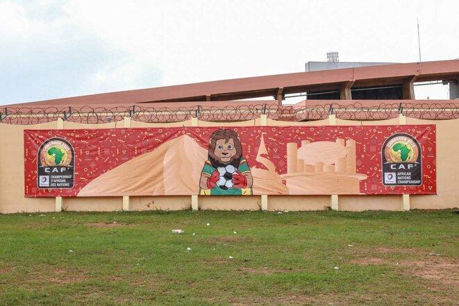 """Des affiches à l'effigie de """"Tara"""", la mascotte de la Coupe d'Afrique des nations, sur l'enceinte du stade omnisports de Yaoundé en janvier 2021. © Photo Daniel Beloumou Olomo / AFP"""