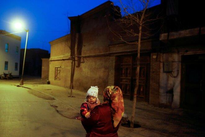 Une femme porte un enfant la nuit dans la vieille ville de Kashgar, dans la région autonome ouïghoure du Xinjiang, en Chine, le 23 mars 2017. REUTERS/Thomas Peter/File Photo