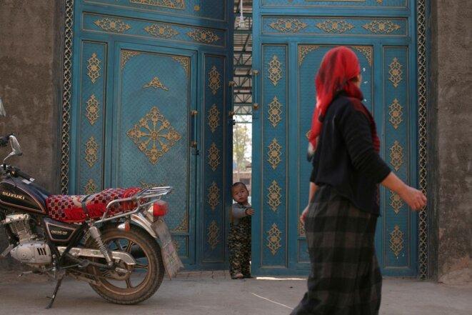Un enfant regarde par une porte alors qu'une femme ouïghoure passe dans un quartier résidentiel de Turpan, dans la région autonome ouïghoure du Xinjiang, le 31 octobre 2013. REUTERS/Michael Martina/File Photo