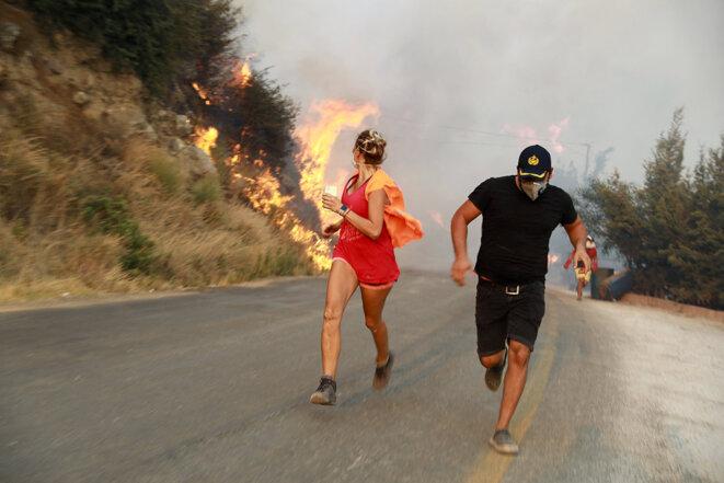 Des habitants fuient les incendies de forêt à Mugla en Turquie le 3 août 2021. © Photo Ali Balli / Agence Anadolu via AFP