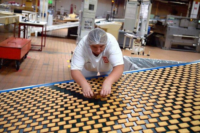 """Une employée sur la ligne de production des """"Petit Beurre"""" de la biscuiterie LU à La Haye-Fouassière, près de Nantes, en 2018. © Photo Loïc Venance / AFP"""