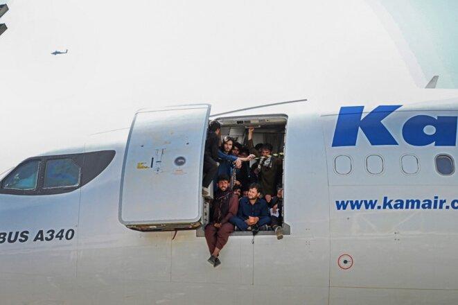 Des Afghans dans un avion situé sur le tarmac de l'aéroport de Kaboul le 16 août 2021. © Wakil Kohsar/AFP
