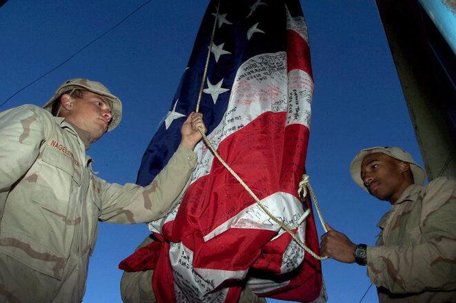 Aéroport de Kandahar, Afghanistan, le 18 décembre 2001. Deux marines américains hissent un drapeau signé par des proches des victimes du 11 septembre 2001. © Photo de Rick Loomis / LA Times  / AFP