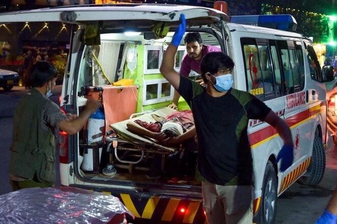 Une ambulance transporte un homme blessé à l'hôpital après deux puissantes explosions, à l'extérieur de l'aéroport de Kaboul le 26 août 2021. © Photo de Wakil Kohsar / AFP
