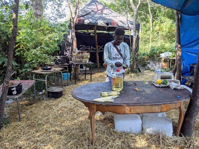 Dans le camp, Abdou Salah se prépare un kiwi. Les exilés dépendent des distributions des associations pour se nourrir. © Photo Rémi Yang /Mediapart