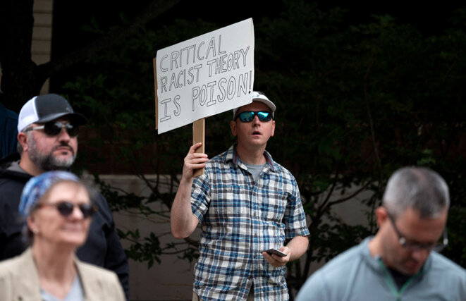 Un homme brandit une pancarte lors d'un rassemblement contre la « théorie critique de la race » dans le comté de Loudoun à Leesburg en Virginie, le 12 juin 2021. © Photo Andrew Caballero-Reynolds / AFP