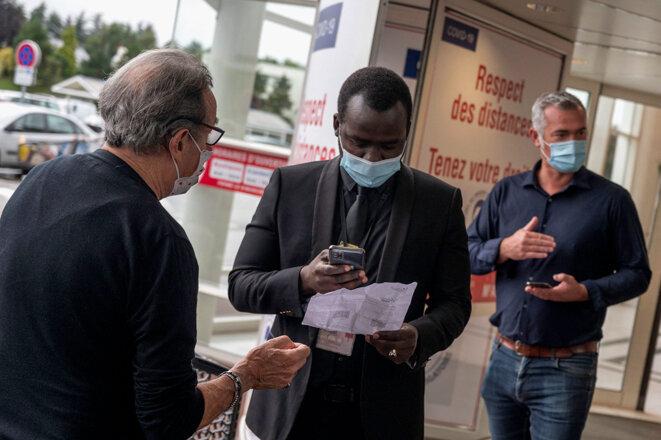 Un agent de sécurité contrôle les passes sanitaires des clients d'un centre commercial à Nantes, le 9 août 2021. © Photo Estelle Ruiz / Hans Lucas via AFP