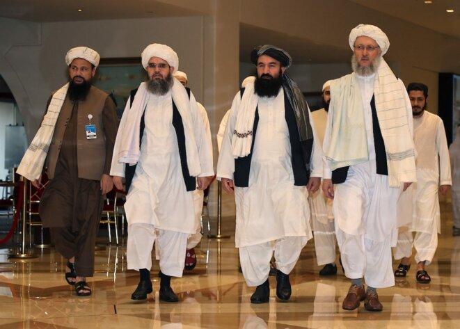 12 août 2021. Le chef de la délégation des talibans Abdul Salam Hanafi (à droite), accompagné de responsables talibans dans le hall d'un hôtel lors des pourparlers à Doha, la capitale du Qatar. © Karim Jaafar / AFP