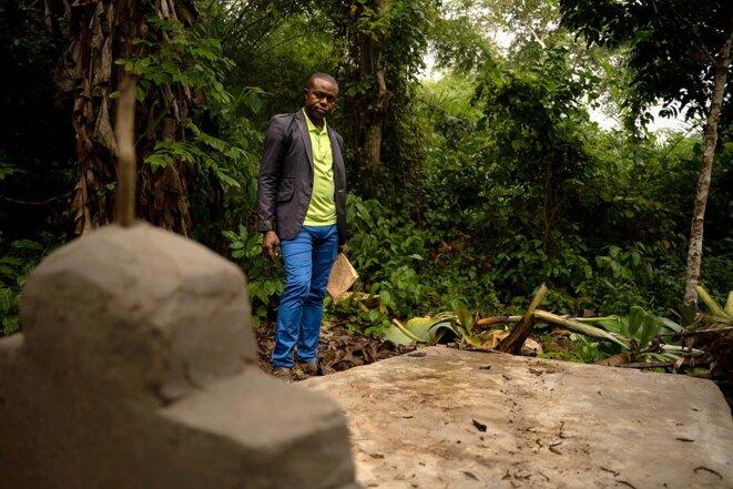 Eddy se recueille sur la tombe de son frère, Blaise Mokwe, tué par des membres de la sécurité de gardiennage de la société Feronia, dans le village de Lokutu (RDC), le18 juillet 2021. © Photo Anthony Fouchard / Disclose