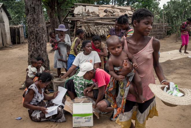 Des habitants d'Ifotaka (Madagascar) reçoivent des suppléments alimentaires pour enfants dans le cadre d'un projet de lutte contre la malnutrition de l'ONG française Acted, le 14 décembre 2018. © RIJASOLO / AFP