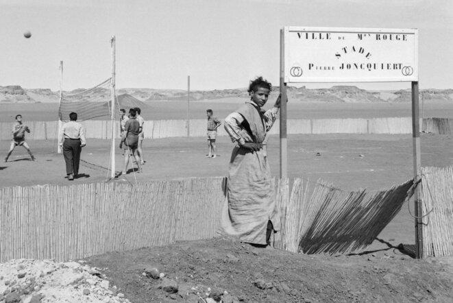 Des techniciens français de la Compagnie de recherche et d'exploitation pétrolière au Sahara (CREPS) jouent au volley-ball sur la base pétrolière d'Edjeleh Maison-Rouge, dans le désert algérien. Mars 1957. © AFP