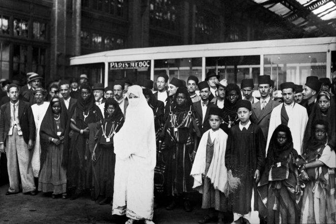 Des membres d'une délégation de personnes venant des colonies françaises à leur arrivée à Paris pour l'exposition internationale de juin 1937. © Photo France presse voir / AFP