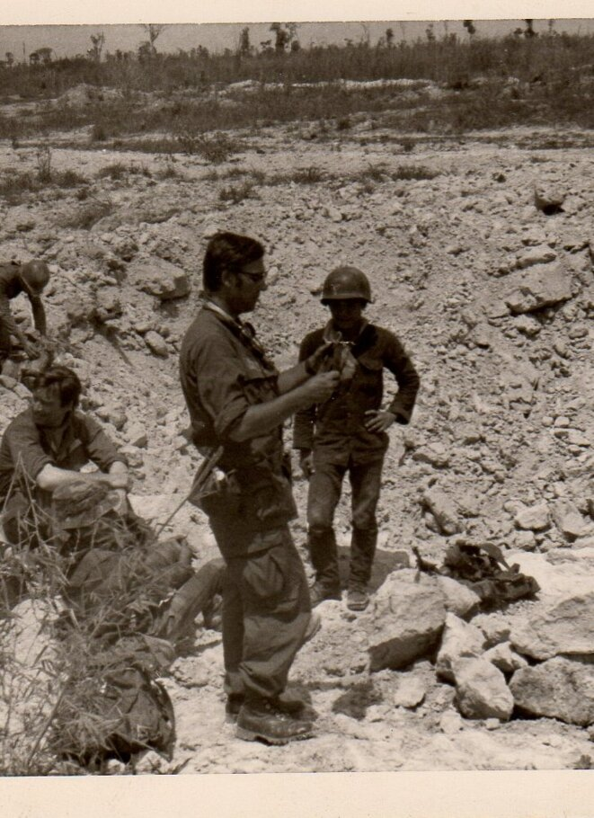 Lucien (in the foreground) in Vietnam in 1972, examining a crater left by a bomb dropped from a US B52 plane. © DR