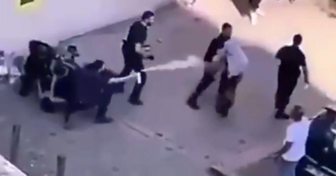 Capture d'écran de la vidéo montrant une femme qui proteste contre l'interpellation de son fils et qui reçoit un jet de gaz lacrymogène en plein visage de la part d'un policier.
