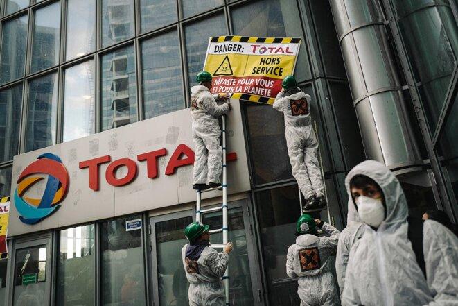 Action de militants d'ATTAC sur les vitres du siège Total à La Défense, le 12 octobre 2019. © Photo Lucas Barioulet / AFP