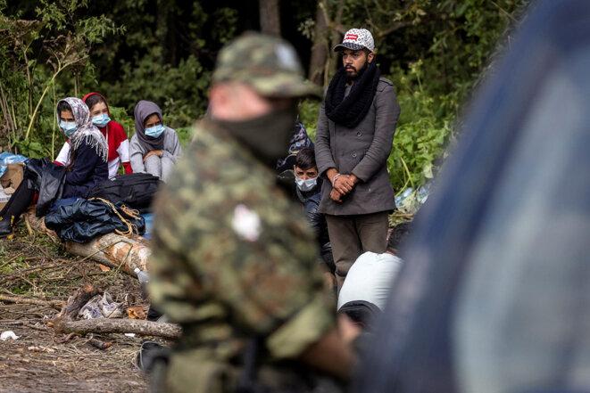 Des personnes migrantes bloquées dans un campement de fortune dans le village d'Usnarz Gorny, dans le nord-est de la Pologne à la frontière avec la Biélorussie, le 20 août 2021. © Photo Wojtek Radwanski / AFP