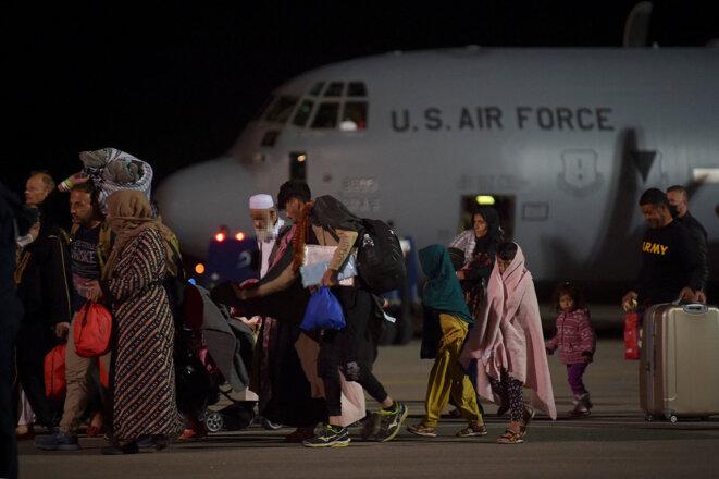 Pristina, Kosovo, le 29 août 2021. Des réfugiés afghans, ayant fuit Kaboul, à leurs arrivée à bord d'un avion de l'armée de l'air américaine. Le Kosovo a proposé d'accueillir temporairement des milliers de réfugiés afghans évacués par les forces américaines de Kaboul jusqu'à leur les demandes d'asile sont traitées. © Photo Armend Nimani / AFP