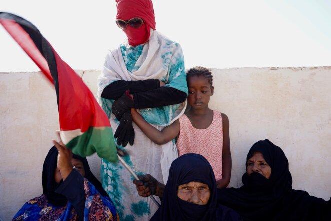 Des femmes brandissent dans le camp de réfugiés de Boujdour le drapeau sahraoui à l'occasion de la 45e fête de l'unité nationale (Tindouf, Algérie, octobre 2021). © Arnaud Marin