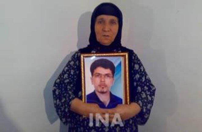 La mère de Farzad Kamangar, tenant son portrait.