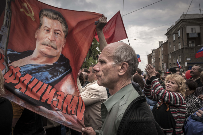 People with soviet flags and a portrait of Josef Stalin attend the May demonstration in Donetsk, Ukraine, Thursday May 1, 2014.