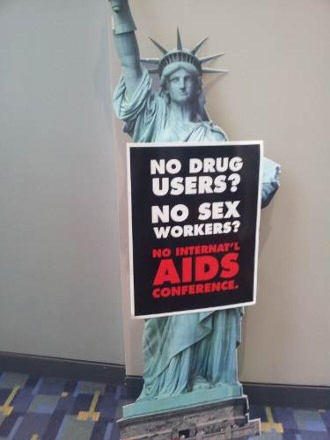 """La photo représente une reproduction en carton de la statue de la liberté, tenant dans sa main une pancarte où on peut lire : """"No Drug Users ? No sex Workers ? No Aids Conference"""" (Traduction : pas d'usagers de drogues ? Pas de travailleuses du sexe ? Pas de conférence). La législation américaine a découragé de nombreux drogués et de nombreuses putes de participer à cette conférence, alors que leurs paroles y est normalement valorisées. Quelle légitimité ont dès lors les discours qui se tiennent © Mérôme Jardin - Image en licence Creative Commons - Attribution - Pas d'utilisation comerciale - Reproduction avec les mêmes"""
