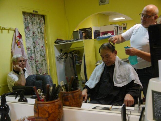 Nordine Diffalah coiffe Philippe, un ouvrier PSA, en discutant avec son cousin Abdelkrim