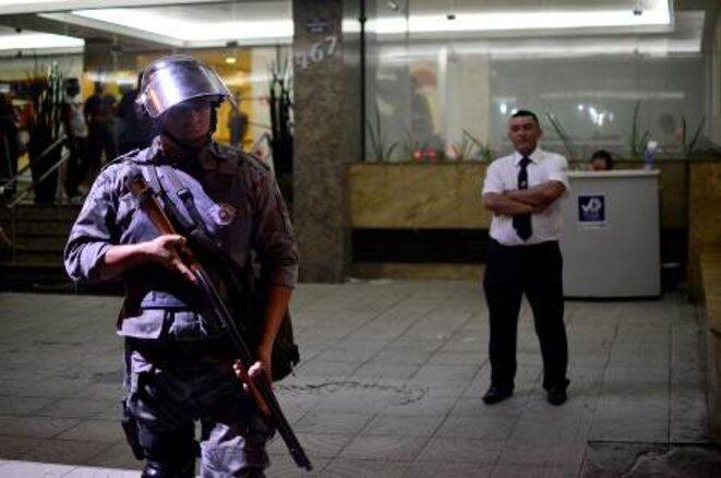 Un flic protège une banque avec un fusil à pompe