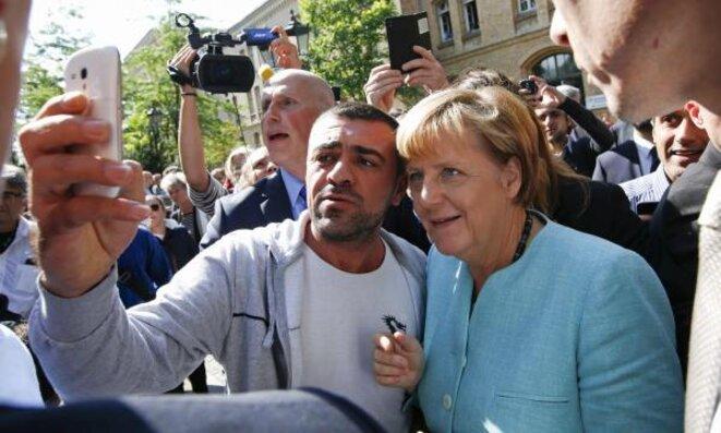 Angela Merkel, le 10 septembre, fait un selfie avec un réfugié lors de la visite d'un centre d'accueil à Berlin. © Reuters