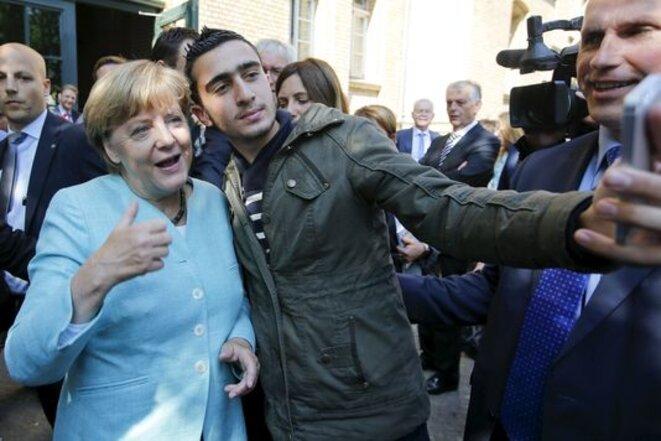 La chancelière allemande, Angela Merkel, prend un selfie avec un migrant, devant un camp de réfugiés à Berlin, le 10 septembre.