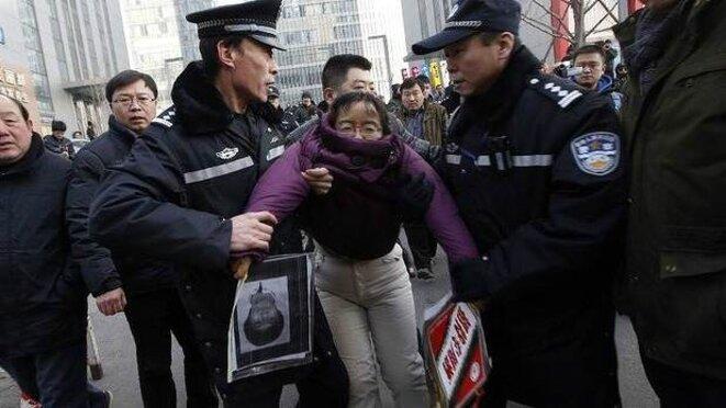 Une manifestante, venue soutenir Xu Zhiyong, est arrêtée près du tribunal.