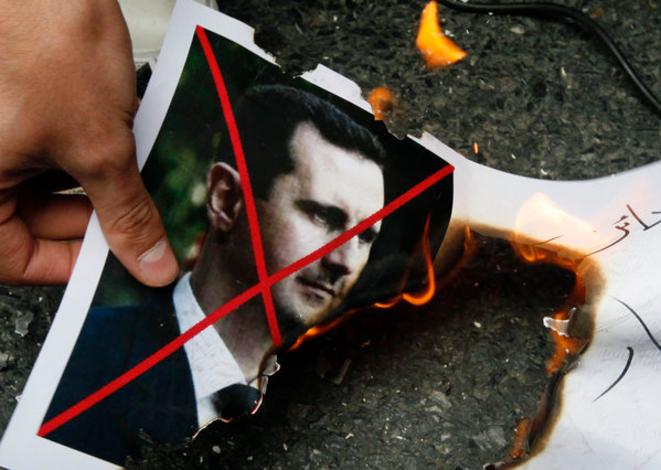 Une photo du président Bachar el-Assad est brûlée par des manifestants à Istanbul (Turquie). © Reuters