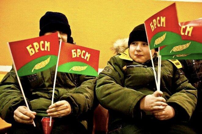 Ecoliers brandissant des drapeaux du BRSM. © Laurent Geslin