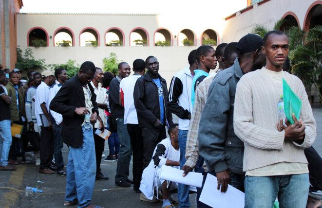 Des Haitiens faisant la queue pour entrer dans un centre d'hébergement.
