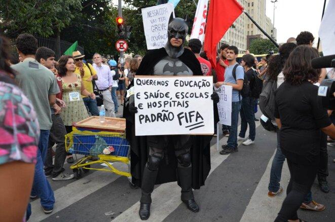 Manifestation du 15 mai à Rio. Batman et sa pancarte: «Nous voulons l'éducation et la santé, des écoles et des hôpitaux»